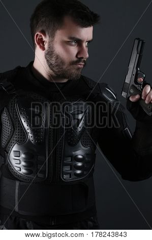 Super Cops- man holding a gun on a gray background