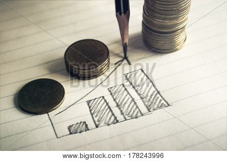 pencil drawing business graph on notebook paper with coins business concept.