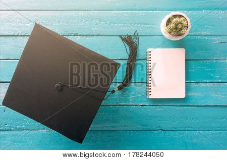 graduation cap hat on blue wood table with Empty notebook view from above.