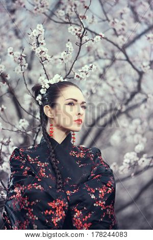 Attractive asian woman wearing kimono standing in blossoming garden. Gorgeous creative portrait outdoor on the nature. Girl looking away