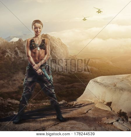 Riot girl on a rocky ledge with a gun