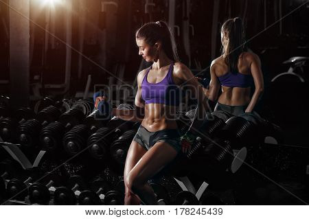 sexy busty young woman workout training with dumbbells in gym