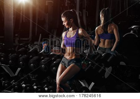 Sexy sporty woman exercising in gym with dumbbells