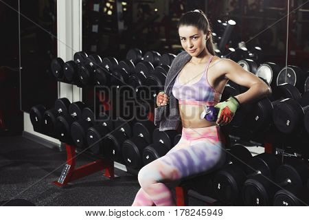 Fitness girl with towel and shker relaxing in the gym