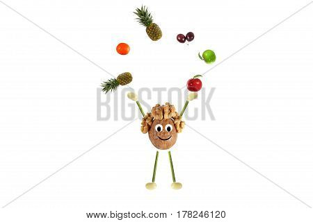 Healthy eating. Funny little man of the walnut juggling with fruits and vegetables
