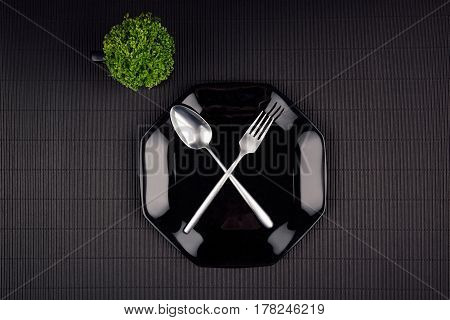 Dark modern minimalistic restaurant menu mock up with black glossy plate spoon fork and green plant top view.
