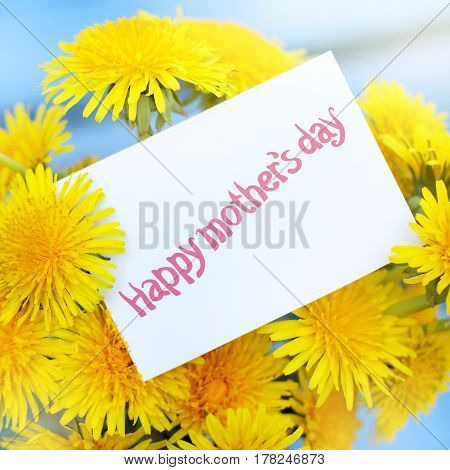 Bouquet of flowers of a sunny dandelion with a note / happy mothers day