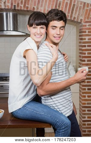 Young woman sitting on kitchen worktop and embracing man