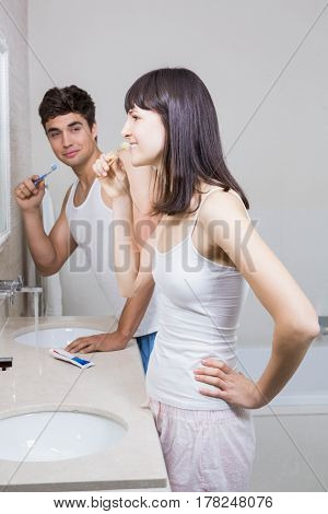 Bathroom routine for happy young couple brushing teeth
