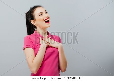 Surprised funny teenage girl showing empty copy space with her finger grey background. Happy