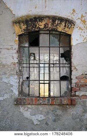 Old window with broken panes on the wall of an industrial old building