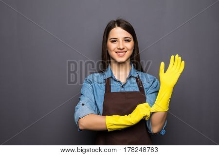 Cheerful Housewife Putting On Gloves Before Cleaning