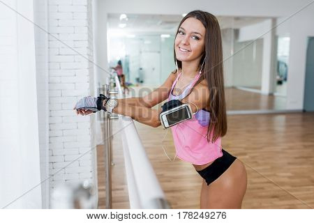 Sexy Athletic Young Woman With Headphones Relaxing In The Gym