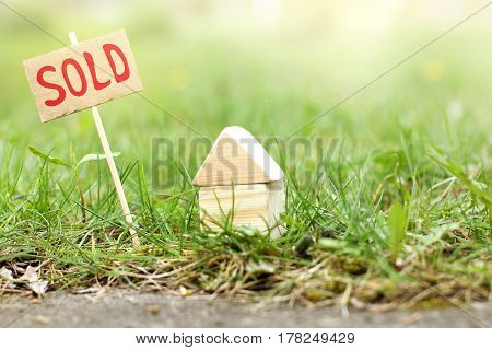 Layout of a wooden house on the lawn near the road with a sign / real estate SOLD