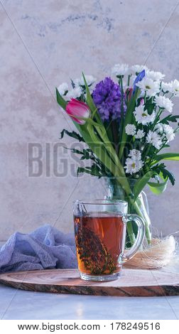 Cup Of Tea With Thyme And Bouquet Of Flowers On Background. Spring Concept