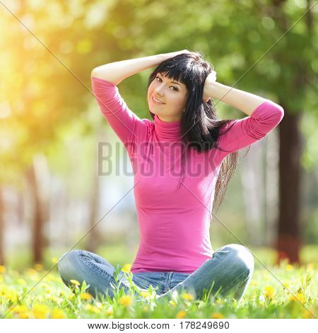 Cute woman in the park with dandelions. Beauty nature scene with colorful background, trees and flowers at spring season. Outdoor lifestyle. Happy smiling woman relax on green grass