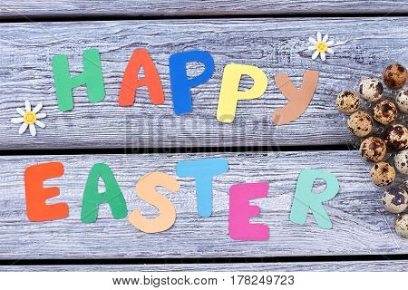 Happy Easter cut letters. Festive greetings and quail eggs. Warmest congratulations for holiday.