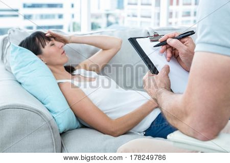 Woman consulting a therapist in the clinic and therapist writing down his notes