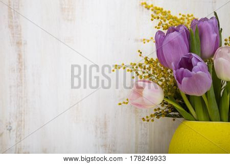 Bouquet Of Tulips In A Yellow Vase On A Wooden Background.