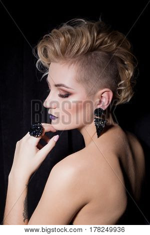beautiful sexy young woman with blond hair with a short haircut with bright makeup and fashion bizhuterieyker earrings and ring, fashion jewelry shooting on a black background in the studio hard light