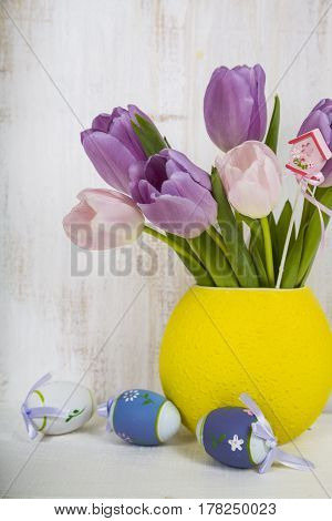 Bouquet Purple Tulips And Easter Eggs On A Light Wooden Table.