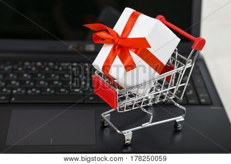 Shopping Cart With Gift Box On Laptop. Concept Of Shopping Online. Buying Gifts For The Holidays Onl