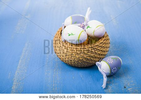 Easter eggs in the basket on a blue wooden table. Easter still life can be used as a postcard.
