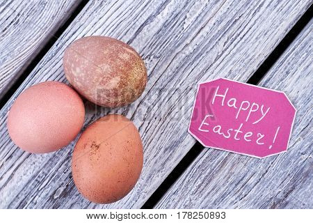 Chicken eggs and congratulatory card. Items on wooden background. Wishes for happy Easter.