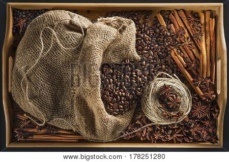 Linen bag with coffee grains, a hank of a cord, a stick of cinnamon, berry of a juniper and fruits of an anisetree on a wooden tray from a bamboo