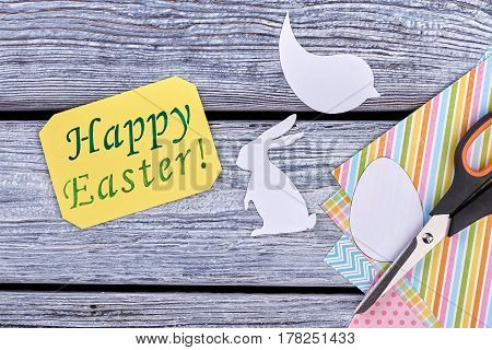 Papercut figures and a greeting card. Colorful stationery on wooden background. Easter holiday decorations.