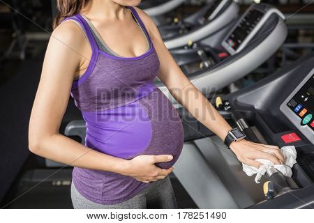 Mid section of pregnant woman cleaning treadmill at the gym