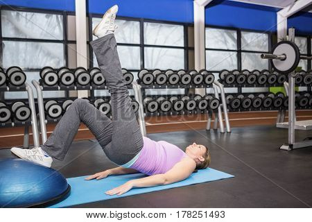 Determined woman exercising with bosu ball at the gym