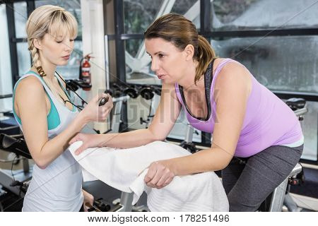 Trainer using stopwatch while pregnant woman is using exercise bike at the gym