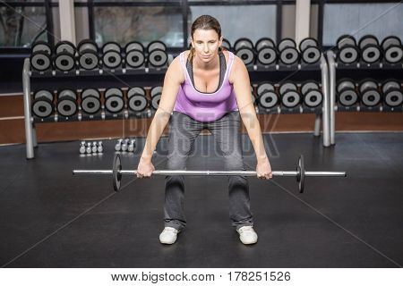 Determined woman lifting barbell at the gym