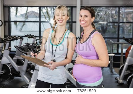 Smiling trainer showing clipboard to pregnant woman at the gym