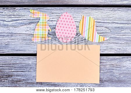 Easter paper crafts, blank card. Colorful cutouts on wooden background. Write greetings and wishes.