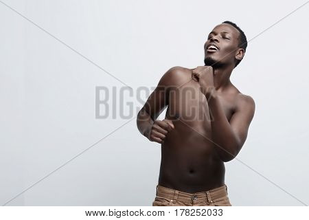 Handsome African American dark- skinned man is dancing enjoying of being himself and the beauty of his athletic body with eyes shut. Moving shirtless against gray studio wall