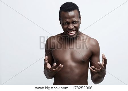 Close up isolated portrait of young annoyed angry African American shirtless man holding hands infurious gesture.Negative human emotions face expressions