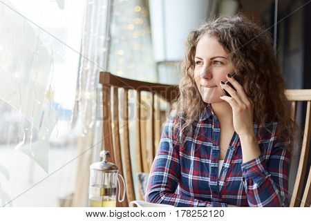 Young charming woman calling cell telephone while sitting alone in coffee shop during free time. Doubtful and indecisive she is looking at the window with thoughtful pensive expression.