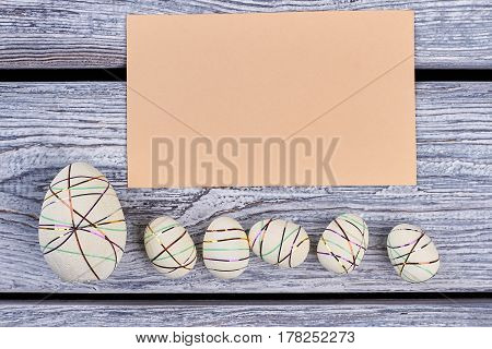 Styrofoam eggs and blank card. Empty paper on gray wood. Warm greetings and kind wishes.