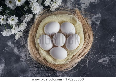 White Chicken Eggs In Easter Nest On Gray Background. Top View