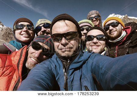 Self Portrait of friendly Team of Mountain Climbers Men and Woman young and elder in protective Sunglasses and high Altitude Jackets and other Gear in old Style tones.