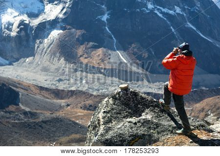 Mountain Climber in warm and red down Jacket taking Picture of Valley and Glacier on photo camera staying on top of Rock
