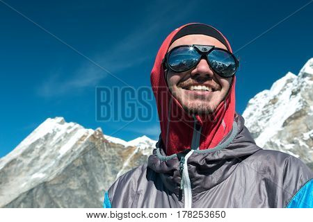 Portrait of happy young Mountain Climber in Sunglasses and windproof Jacket looking up onto Summits and Sun