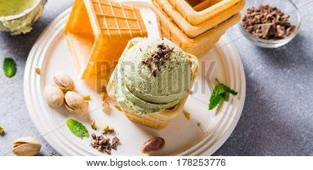 Pistachio ice cream with grated chocolate in waffle cups on gray stone background. Homemade summer food concept. High angle view