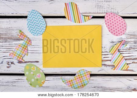 Blank card and Easter cutouts. Colorful paper crafts on wood.