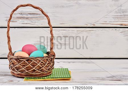 Easter eggs basket and napkins. Wicker basket, white wood background.