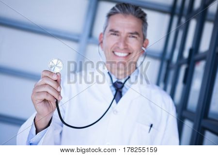 Portrait of male doctor smiling and showing stethoscope in hospital