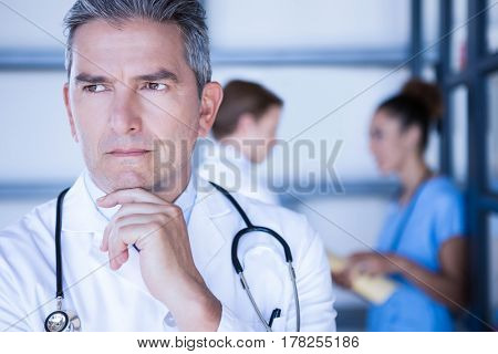Thoughtful doctor standing with hand on chin in hospital