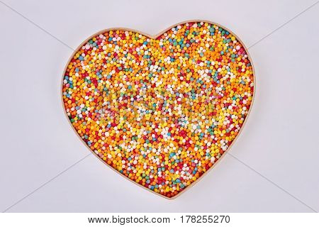 Sprinkle dots, heart shaped box. Sugar sprinkles on white background. Saint valentine present.